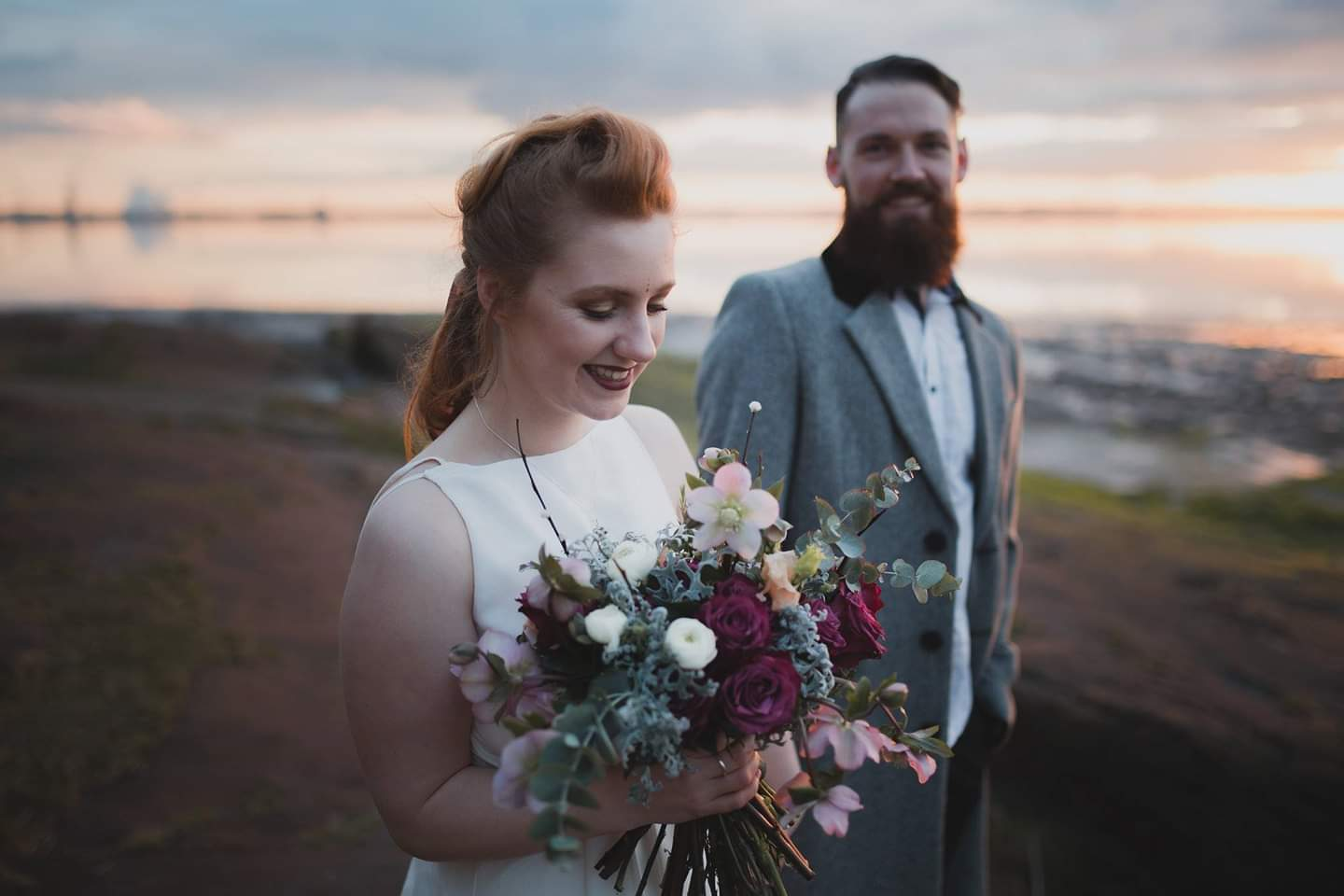 boho bride and groom walking on the beach at sunset in Liverpool