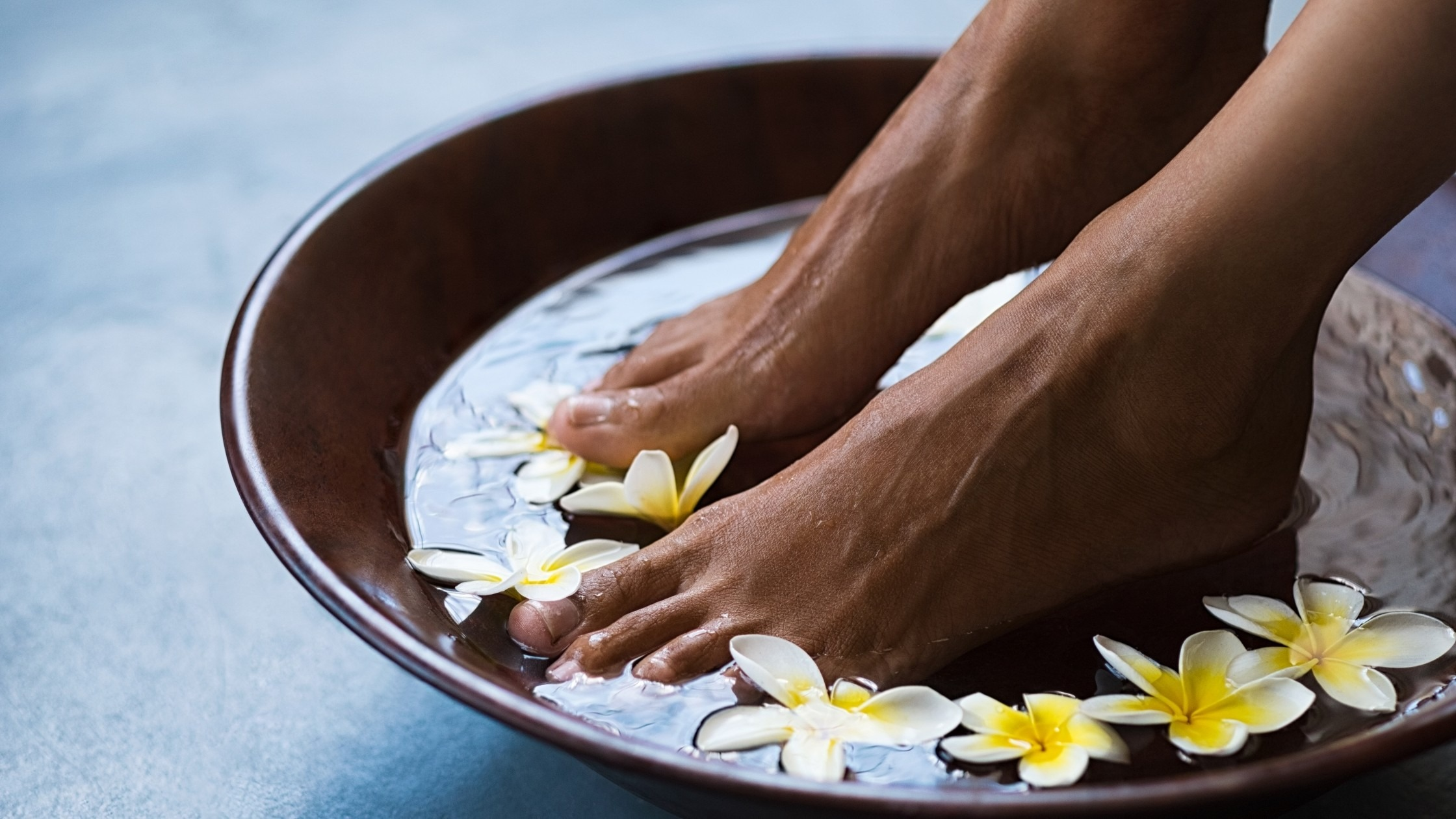 feet soaking in a bowl of water with flowers