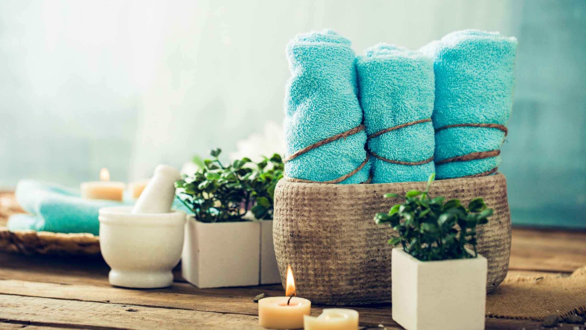 blue bath towels and candles in a bathroom