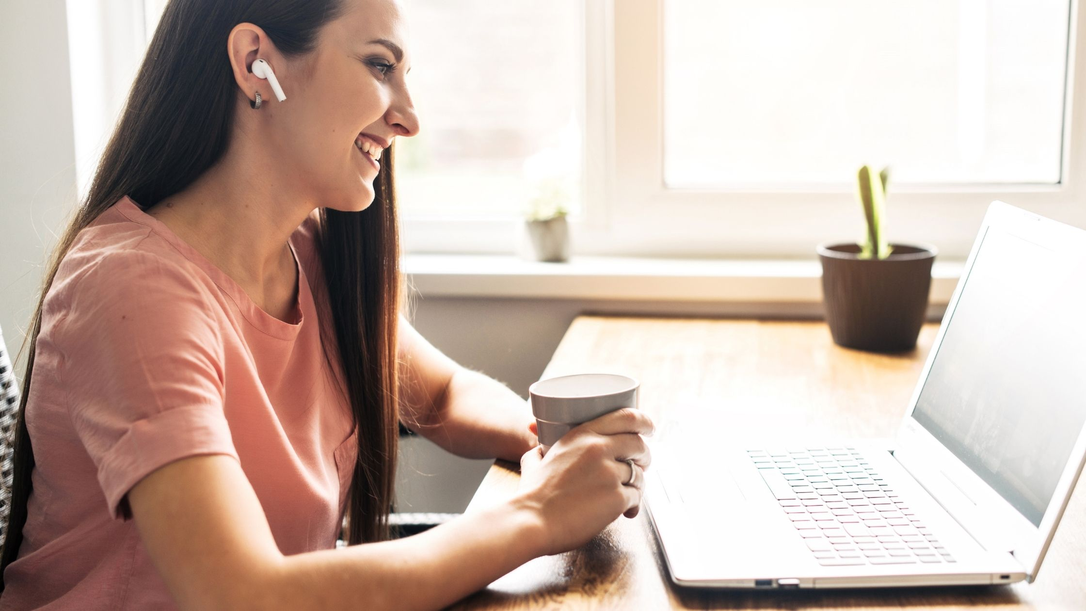 Woman with brown hair wearing ear buds and holding a coffee cup. She is on a zoom call on her laptop.