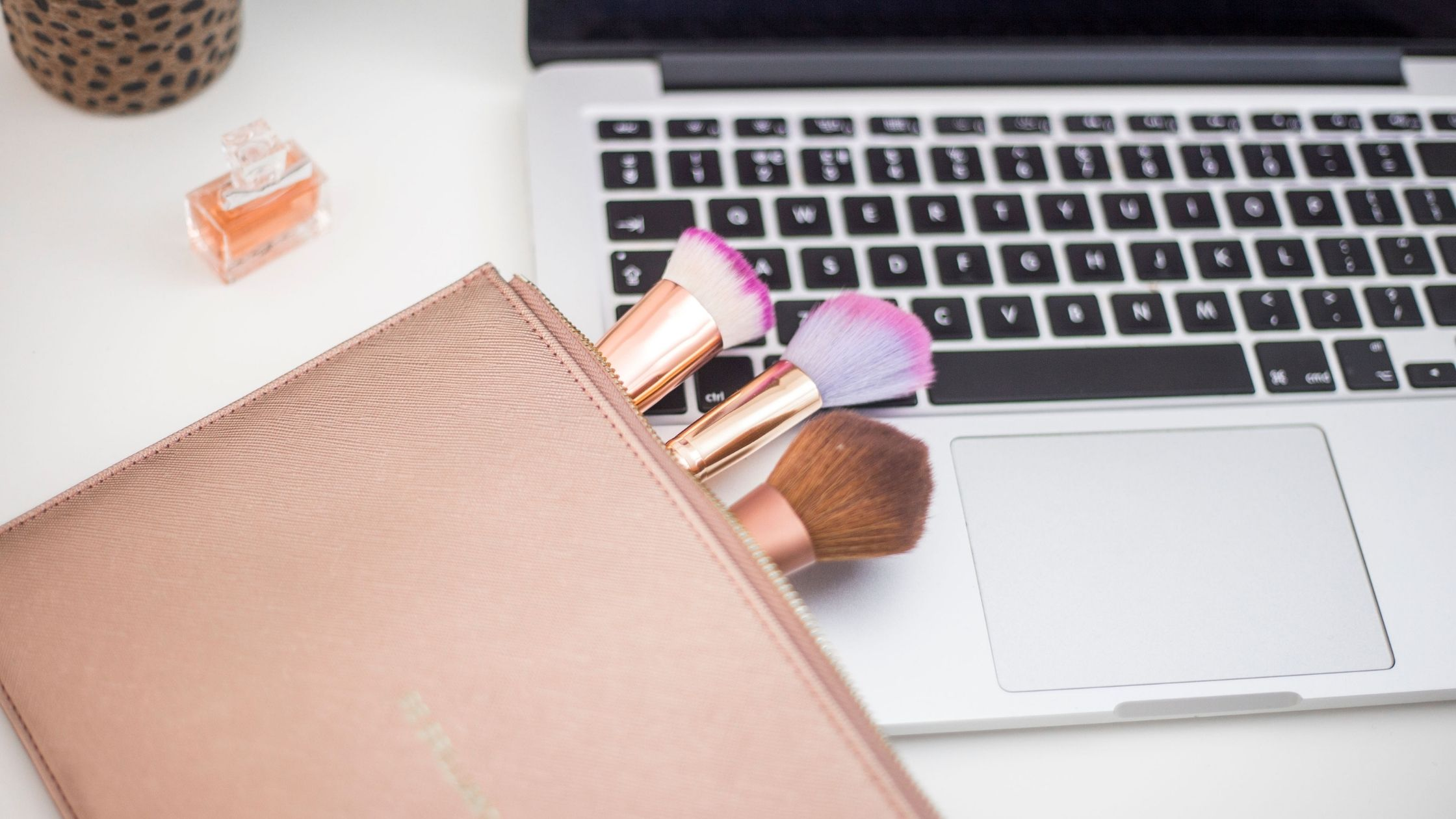 makeup brushes in a pink makeup bag lying on a laptop keyboard