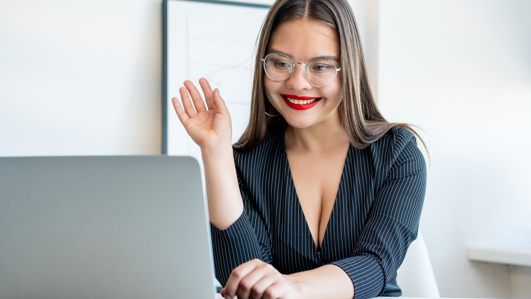 Woman with brown hair parted in the center. She is wearing a pinstripe blouse and red lipstick and glasses. She is waving hello on a zoom call on her laptop.