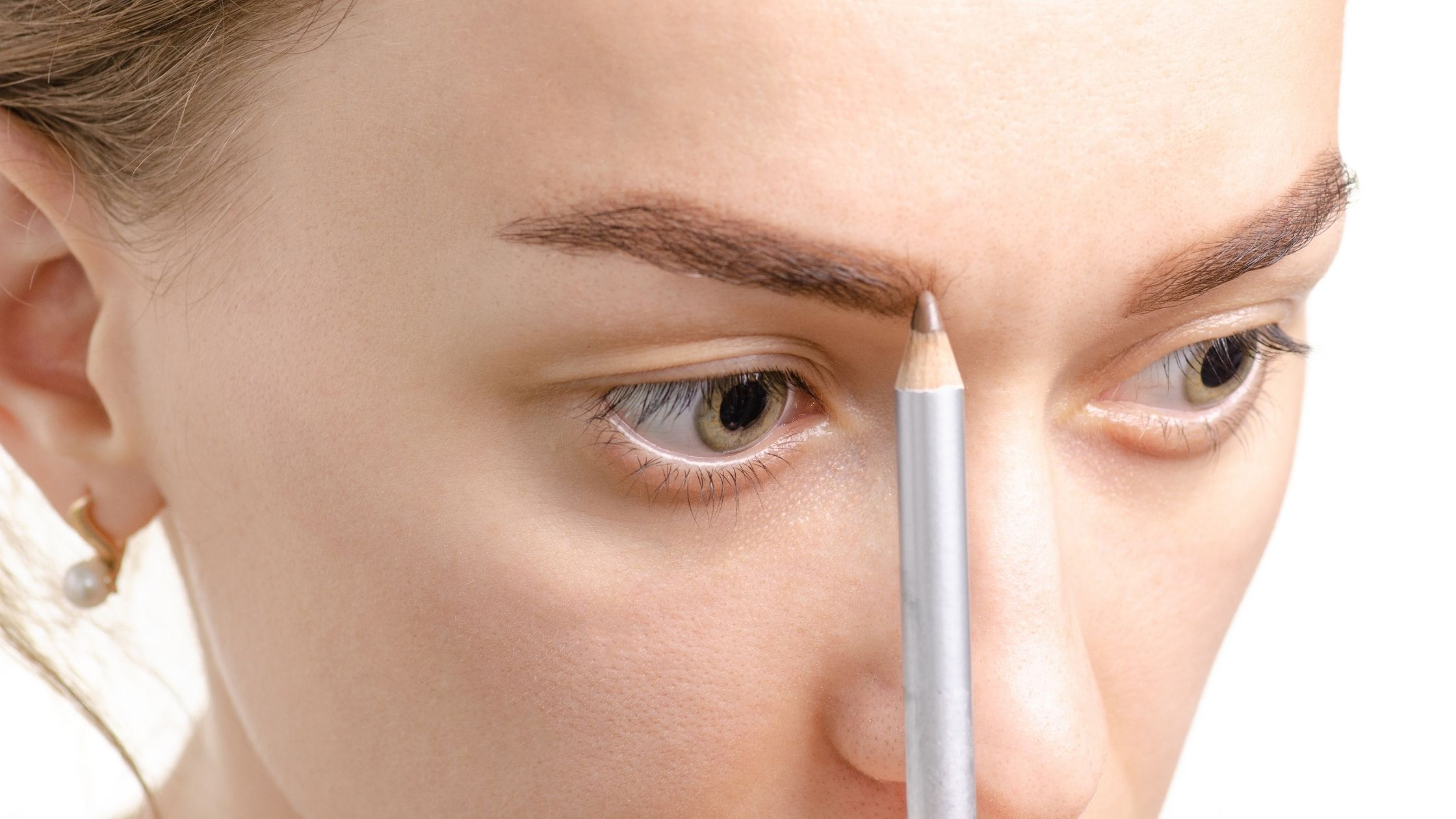 woman using and eyebrow pencil
