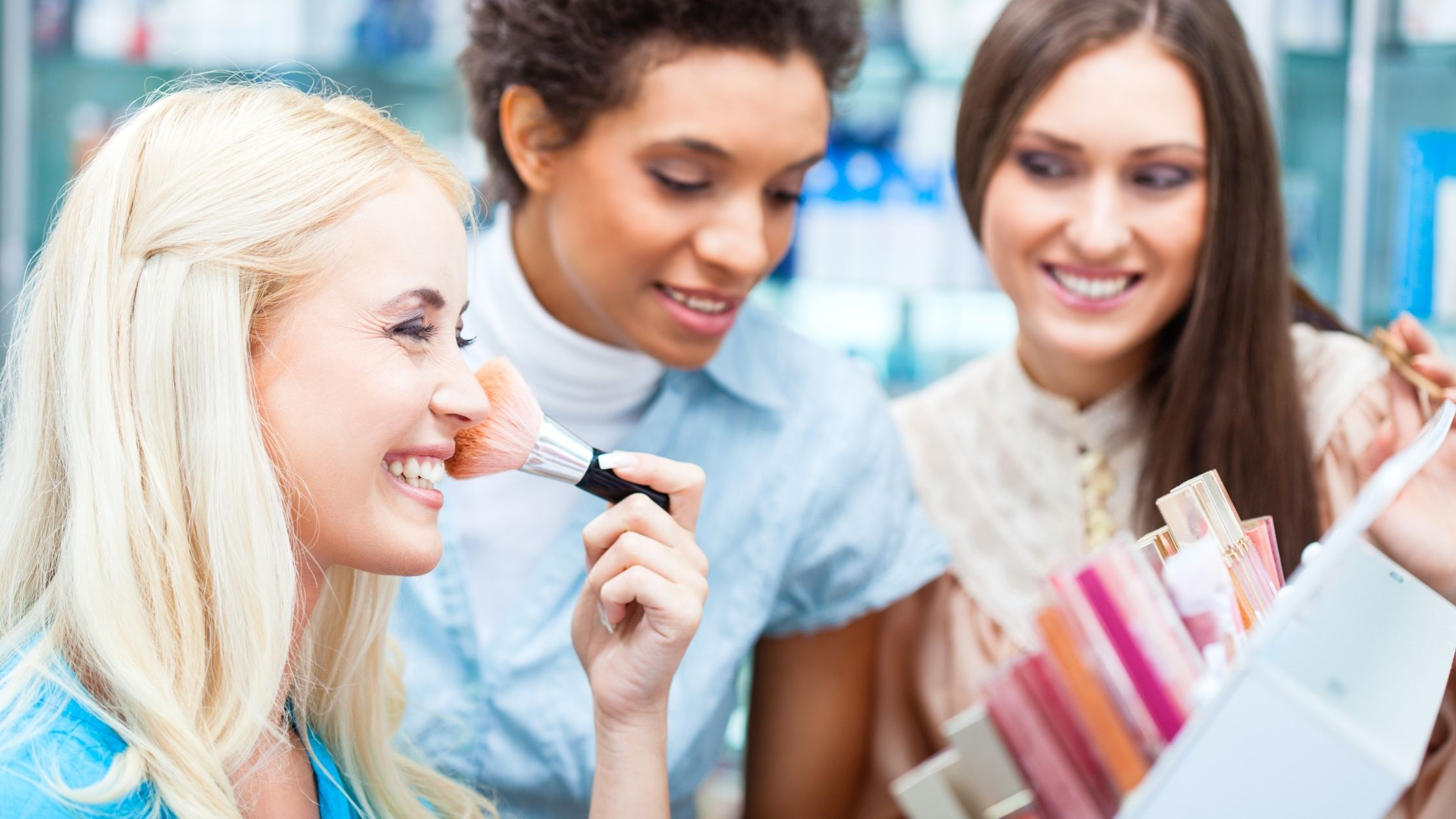 three women trying makeup on in a shop