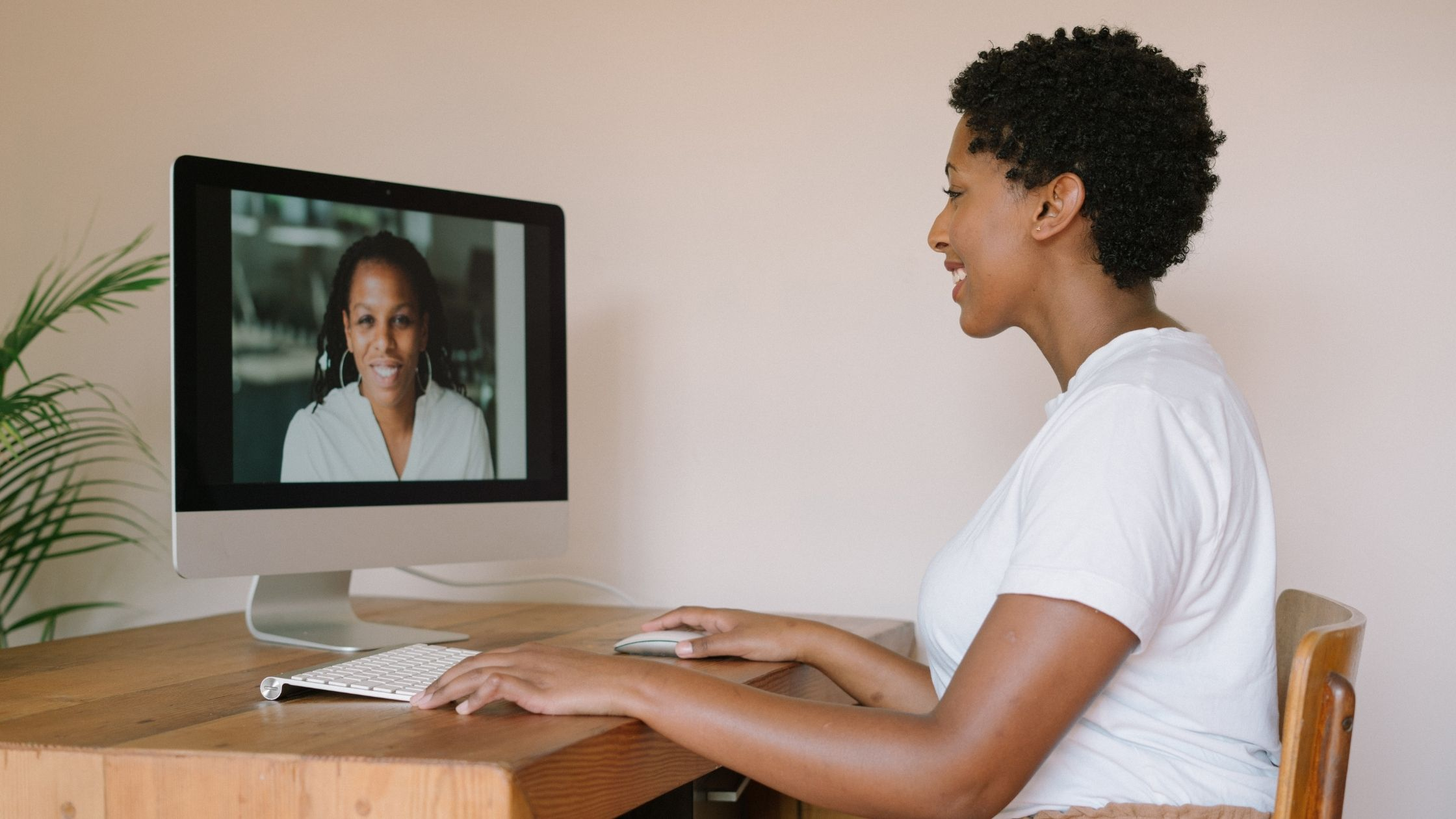 two women are talking on a zoom call on a desktop computer.