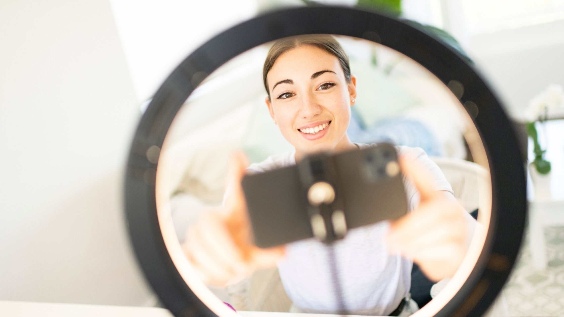 Woman with brown hair that is parted in the middle. She is on a zoom call on her phone, Her phone is on a holder in the center of a ring light.